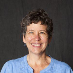 Betty Rozum smiling against a dark gray background